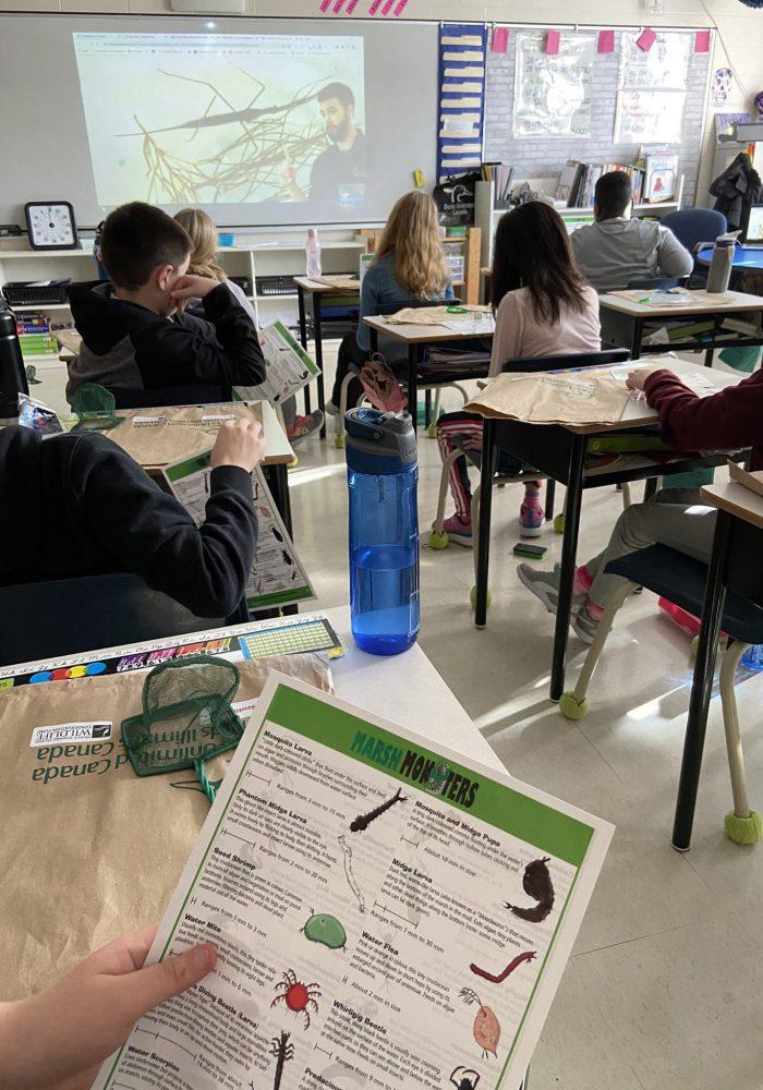 Des élèves suivent l'exposé virtuel de CIC sur les milieux humides en faisant appel à des ressources en classe.